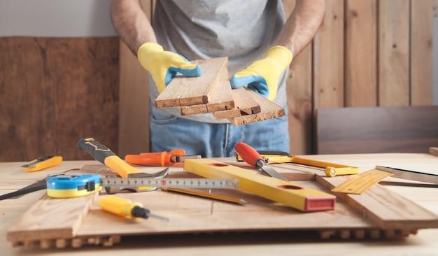 Charpentier tenant des planches de bois