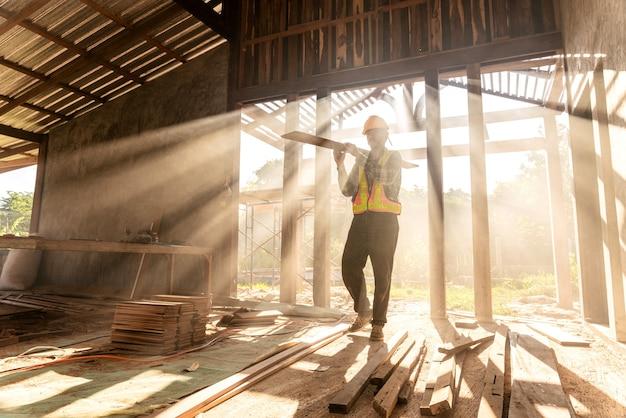 Le charpentier tient des planches en bois sur le chantier de construction