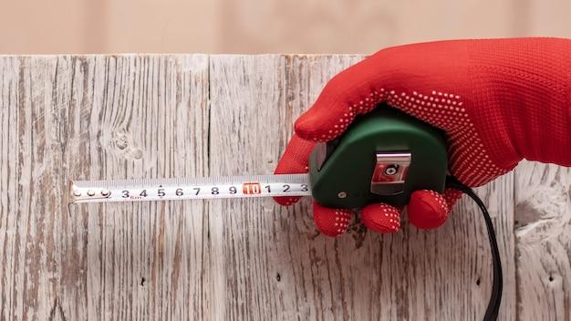 Le charpentier tient un ruban à mesurer à la main sur un fond de planches