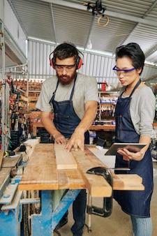 Charpentier travaillant avec apprenti