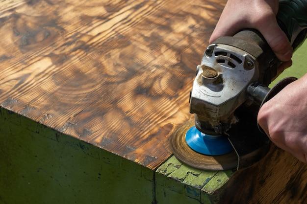 Charpentier travaillant le bois, enlève la vieille peinture