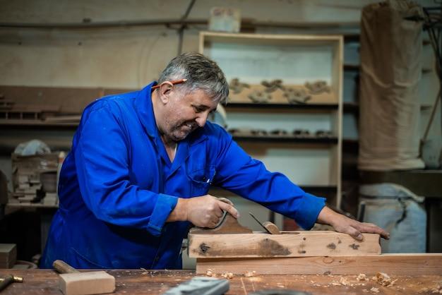 Charpentier travaillant dans l'atelier, un ouvrier rabotant un arbre avec un rabot