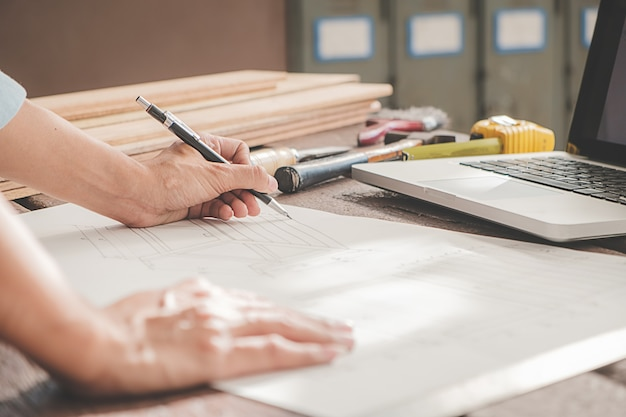 Charpentier travaillant avec des équipements sur une table en bois dans l'atelier de menuiserie. femme travaille dans un atelier de menuiserie.
