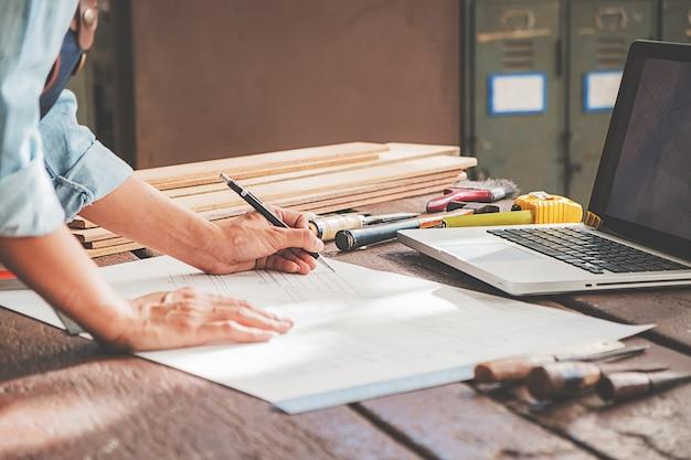 Charpentier travaillant avec des équipements sur une table en bois dans l'atelier de menuiserie.