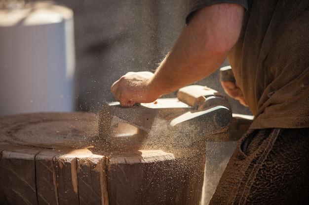 Charpentier travaillant avec une raboteuse électrique sur une souche en bois à l'extérieur