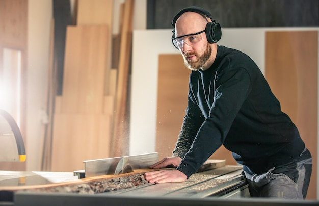 Charpentier travaillant sur une scie à bois dans un atelier de menuiserie, concept industriel