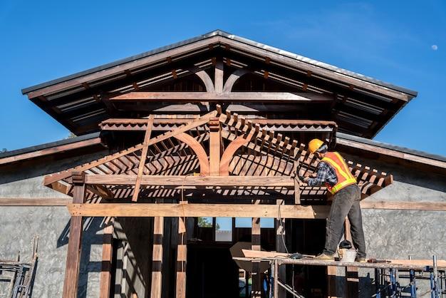 Charpentier travaillant sur la structure du toit sur le chantier de construction