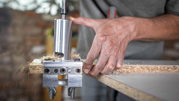 Le charpentier travaille comme un outil professionnel pour percer le bois.