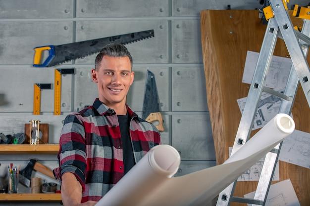 Un charpentier travaille. menuisier étudiant projet de dessin. dans le contexte de l'atelier.