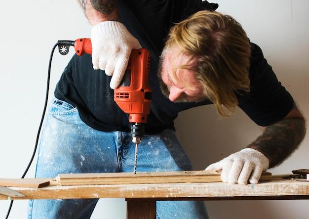 Un charpentier utilisant une perceuse sur un bois