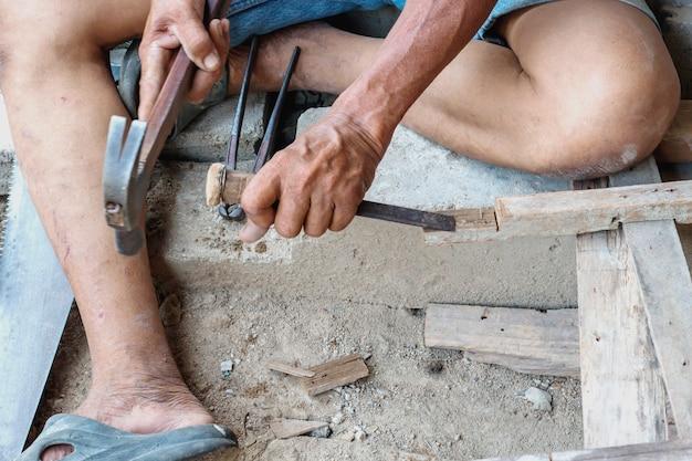 Un charpentier utilisant une règle pour tracer une ligne sur une planche.