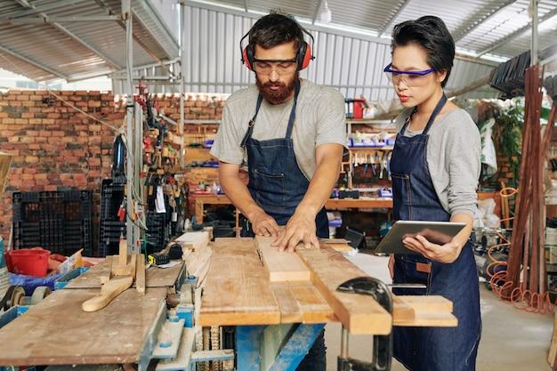 Charpentiers coupant des planches de bois de pin