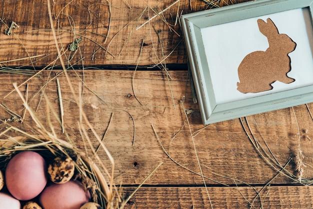 La chasse au lapin ester commence ! vue de dessus des oeufs de pâques colorés dans un bol avec du foin et un lapin de pâques dans un cadre photo allongé sur une table rustique en bois
