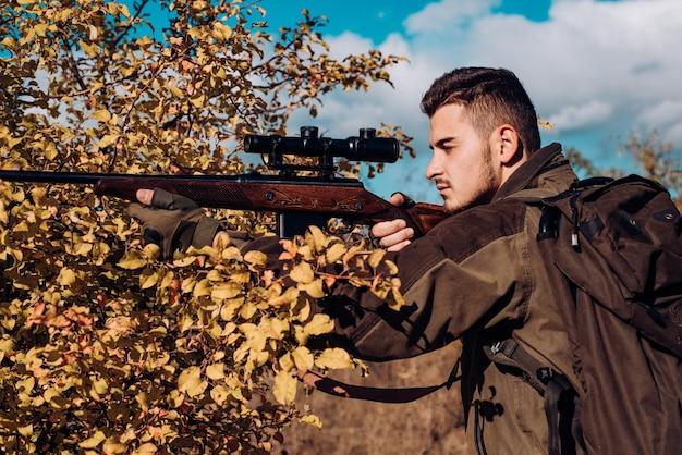 Chasse au printemps chasseur forestier avec fusil de chasse sur chasseur de chasse se déplaçant avec fusil de chasse à la recherche de proies