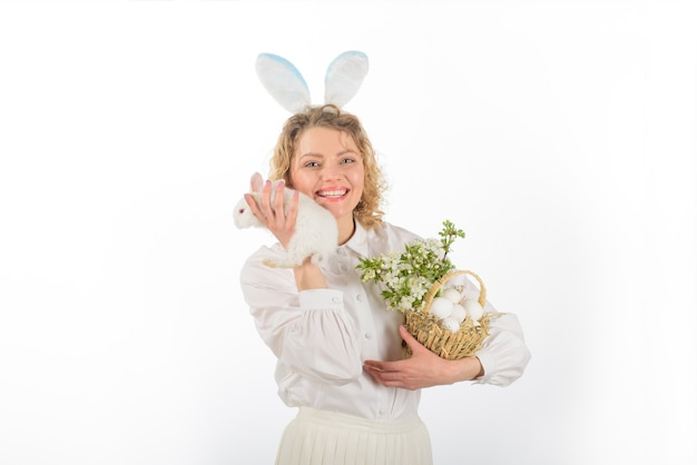 Chasse aux oeufs oeuf de pâques lapin oreilles de lapin fille de pâques dans les oreilles de lapin détient un panier avec des oeufs et pâques