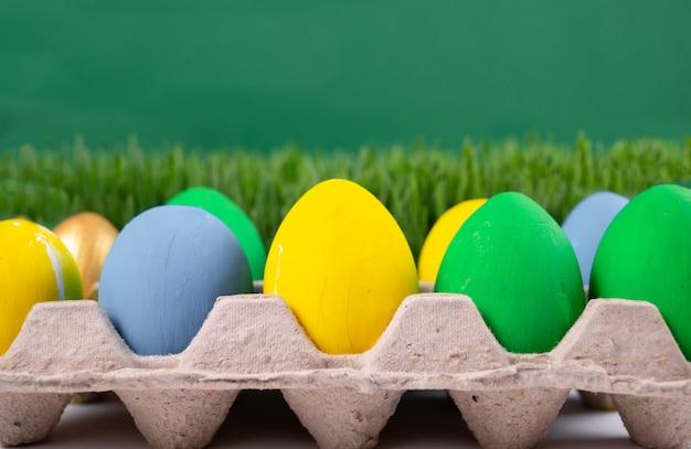 Chasse aux oeufs de pâques. fête de pâques. vous cherchez des œufs de pâques dans l'herbe. de nombreux œufs de pâques peints dans un plateau. fond de vacances de printemps. bannière