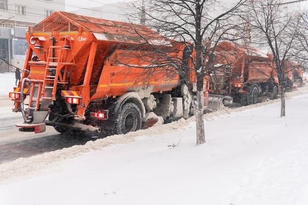 Les chasse-neige enlèvent la neige de la route dans la ville. plusieurs camions nettoient l'asphalte. il neige. mise au point floue.