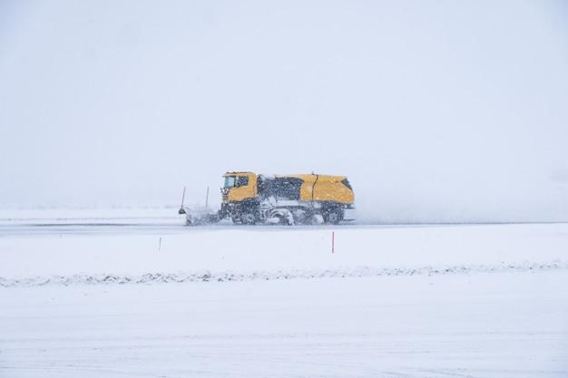Chasse-neige jaune labourant la route couverte de neige dans le blizzard