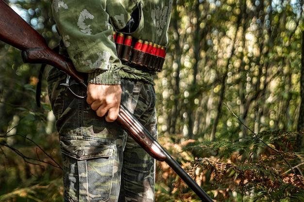 Chasseur avec une arme à la main dans les vêtements de chasse dans la forêt d'automne