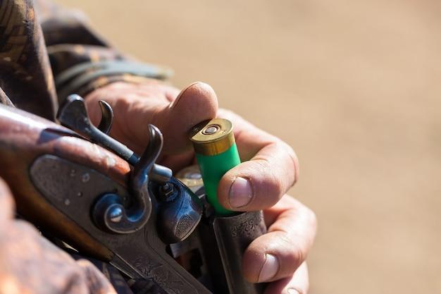 Chasseur de canard avec fusil de chasse marchant dans un pré.