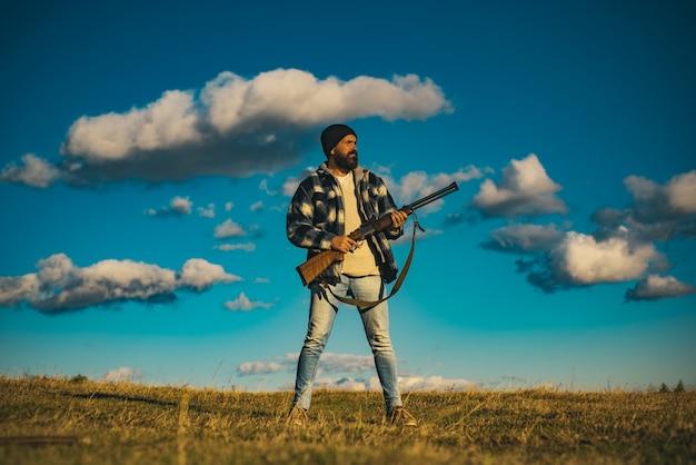 Chasseur avec fusil de chasse en chasse. matériel de chasse pour les professionnels. la chasse est un passe-temps masculin brutal pour les chasseurs.