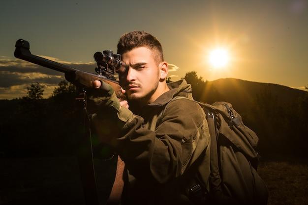 Chasseur avec fusil de chasse en chasse. traquer. équipement de chasse et vêtements de chasse.