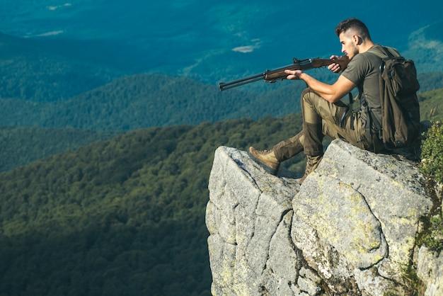 Chasseur avec un fusil de chasse dans un vêtement de tir traditionnel. chasse à la faune. équipement de chasse - chasse