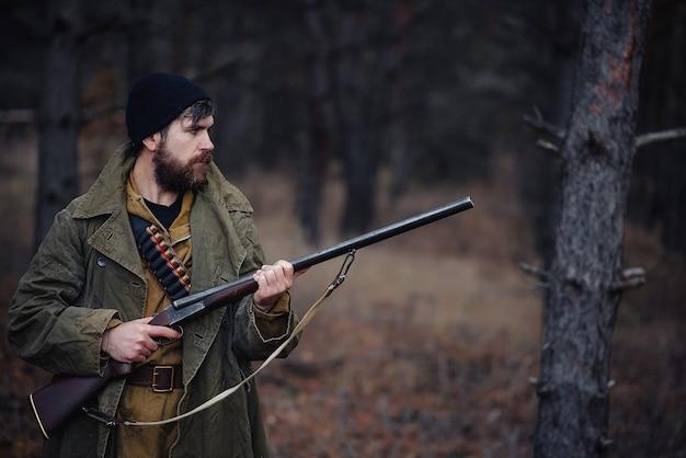 Chasseur d'homme barbu brutal sévère dans un chapeau noir et une veste kaki dans un long manteau tient une arme à feu dans sa main dirigée vers la forêt