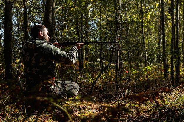 Chasseur en tenue de camouflage avec une arme à feu pendant la chasse à la recherche d'oiseaux sauvages