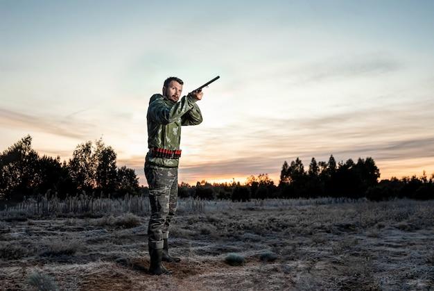 Chasseur en tenue de camouflage avec une arme à feu pendant la chasse