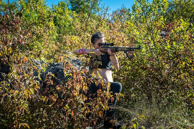 Chasseuse en haut à l'aide d'une arme ou d'un fusil dans la nature, en plein air
