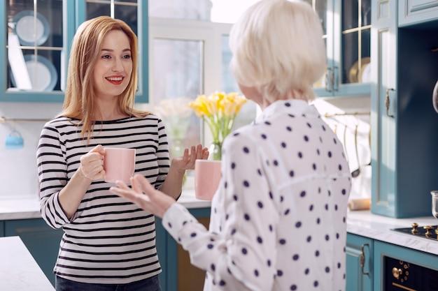 Chat agréable. belle jeune femme discutant avec sa mère âgée dans la cuisine tout en buvant du café dans des tasses roses et en échangeant des sourires
