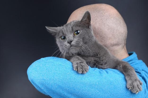 Chat gris assis sur l'épaule d'un homme