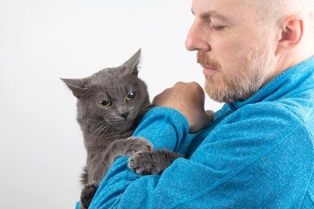 Chat gris tenant la patte de l'homme