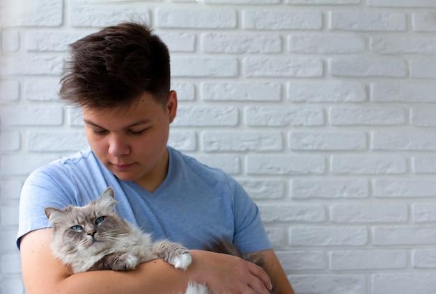 Chat et homme, portrait de chat heureux avec des yeux proches et jeune homme