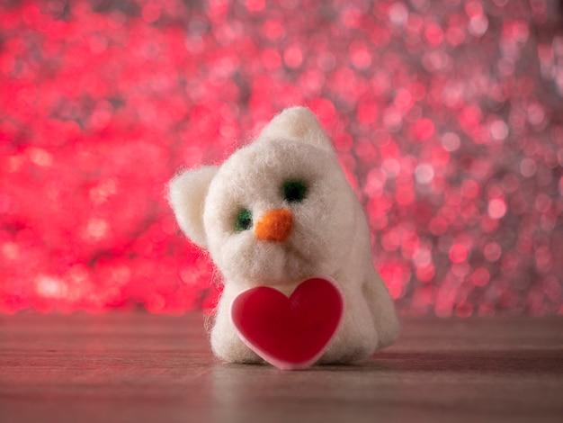 Chat jouet blanc se dresse sur la table avec un coeur rouge sur fond rose