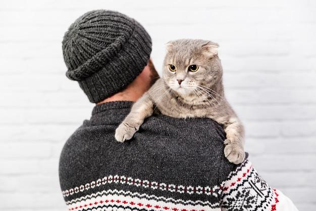 Chat mignon tenu par le propriétaire