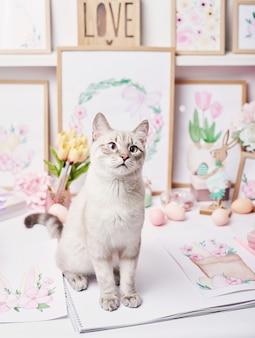 Chat de pâques avec des œufs et des fleurs. chaton gris assis sur la table. carte de voeux de printemps joyeuses pâques. décor de pâques. peintures de printemps aquarelle. lieu de travail du designer et de l'artiste. espace créatif.