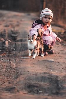 Le chat se promène avec une petite fille dans le parc. marcher avec l'animal à l'automne. chat joue dans les feuilles