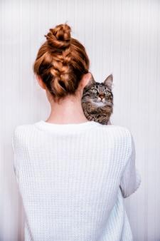 Un chat tigré est assis sur une épaule sur un fond blanc. la fille a le dos tourné.