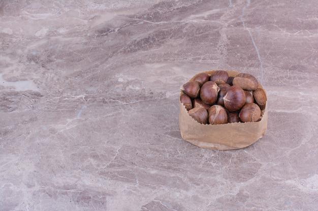 Châtaignes brunes dans une corbeille à papier sur la pierre