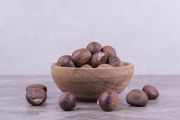 Châtaignes brunes dans une tasse en bois sur la pierre