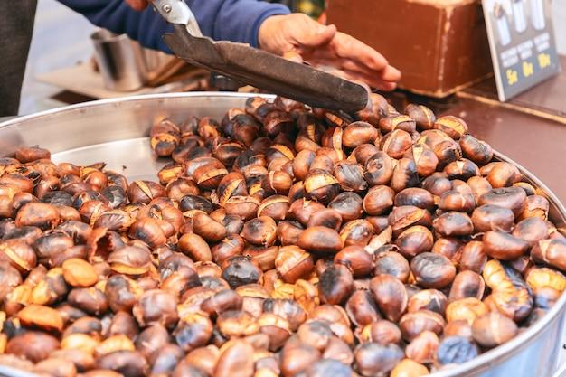 Châtaignes dans une casserole pendant la torréfaction au charbon de bois sur un marché alimentaire de rue torréfaction au charbon de châtaignes