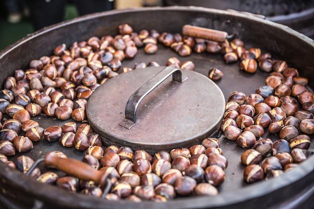 Châtaignes grillées dans une poêle quelque part dans le marché de rue.
