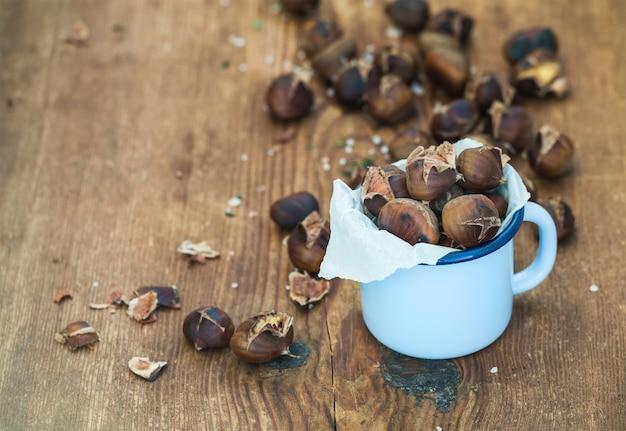 Châtaignes grillées dans une tasse en émail bleu sur bois rustique