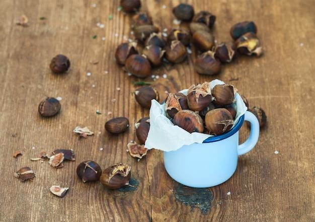 Châtaignes grillées dans une tasse en émail bleu sur une surface en bois rustique