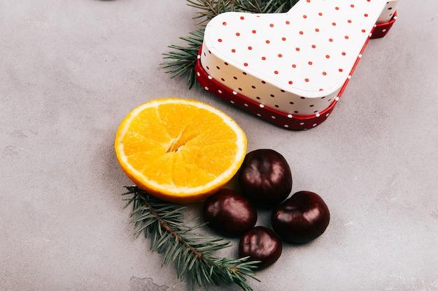 Châtaignes, orange, branche de sapin et boîte actuelle sur sol gris