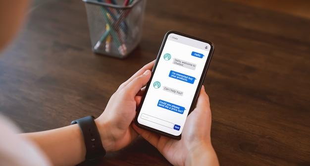 Chatbot numérique et envoyé au destinataire sur mobile, à la main à l'aide d'un smartphone, intelligence artificielle, innovation et technologie