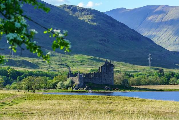 Le château de kilchurn, confié à historic environment scotland, est une structure en ruine sur une péninsule rocheuse du loch awe au crépuscule, à argyll and bute, en écosse.