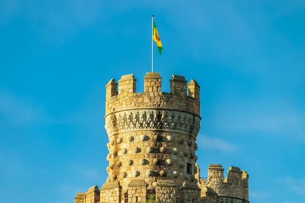 Château médiéval sur la montagne, tour avec drapeau, ciel bleu et nuages. castillo manzanares real madrid. l'europe 